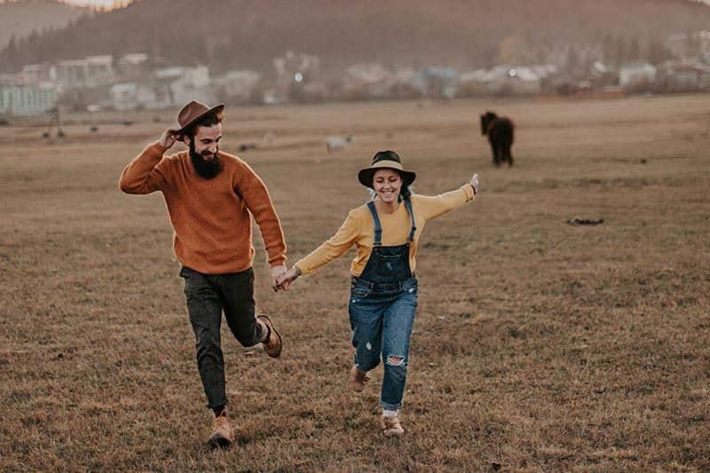 man and woman holding hands and running