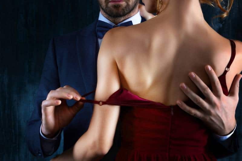 man takes off woman's red dress