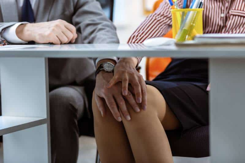 man touches woman knee under table