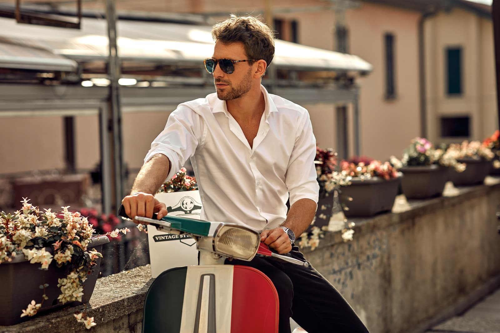 man wearing white shirt and sitting on classic scooter