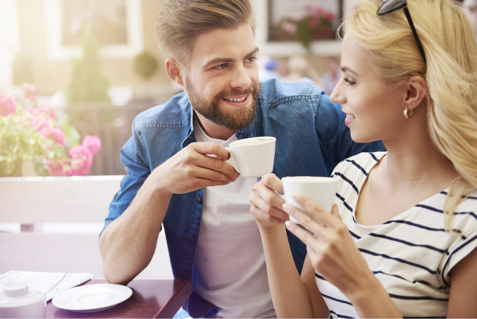 man with beard drinking coffee and talking with woman