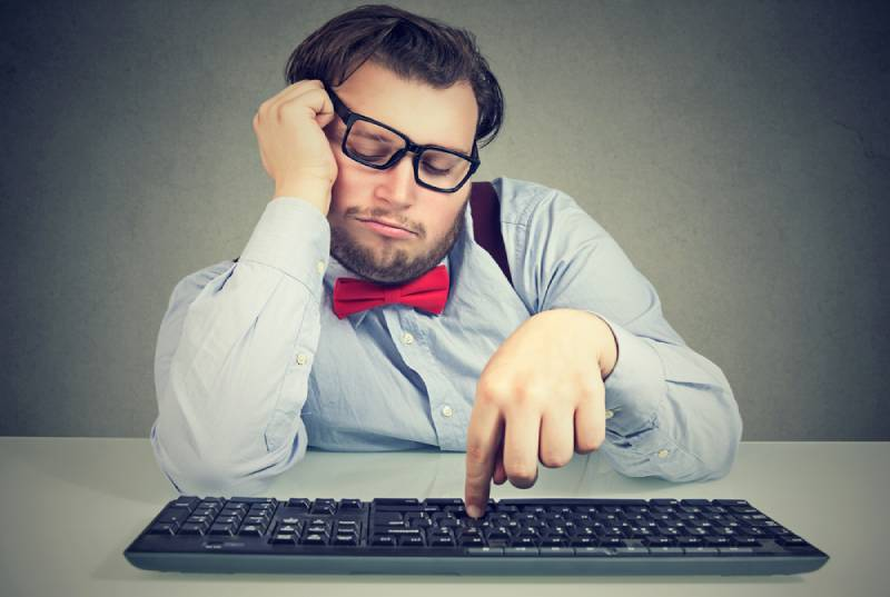 obese man sitting at workplace and procastinating