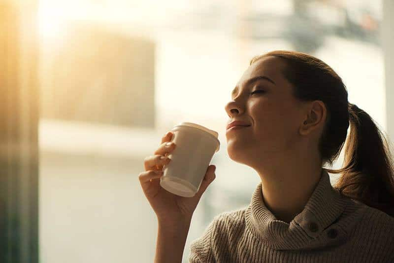 relaxed woman drinking coffee with pleasure