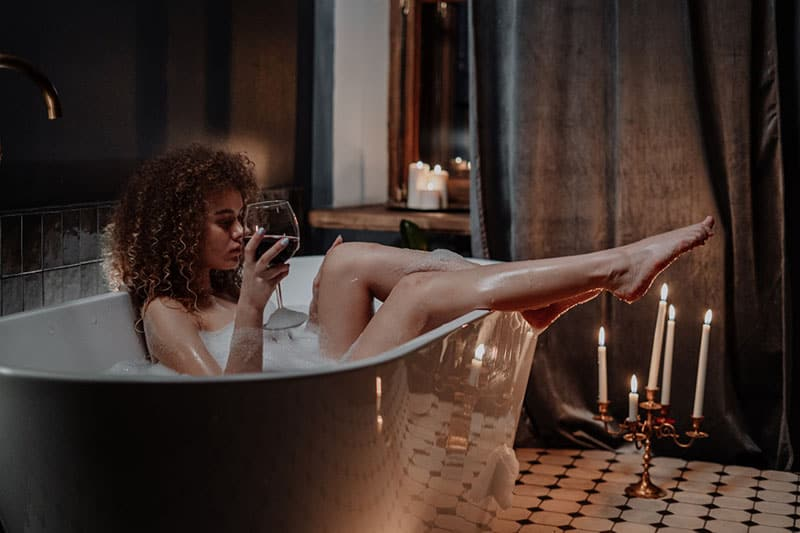 sexy woman having a bath and glass of wine