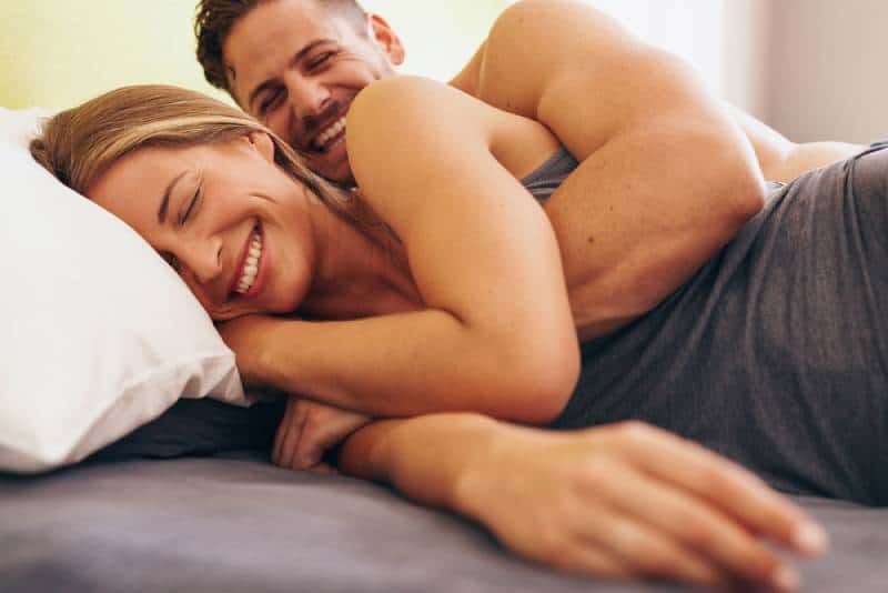 smiling couple waking up in morning