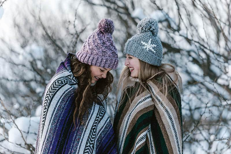 two smiling female friends covered with blanket during winter time