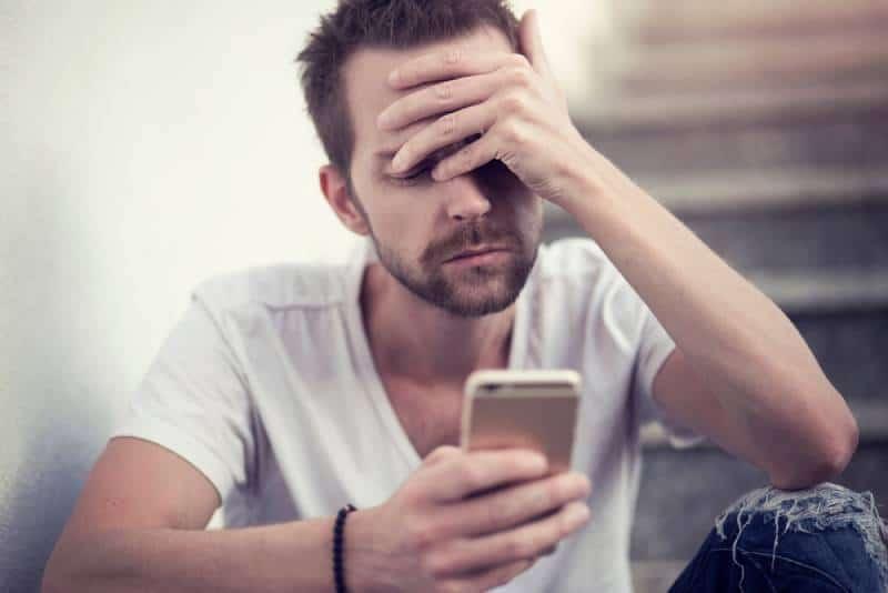 unhappy man looking at his phone