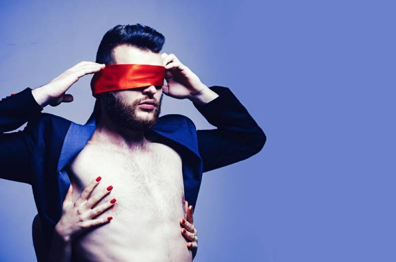 woman covering man eyes
