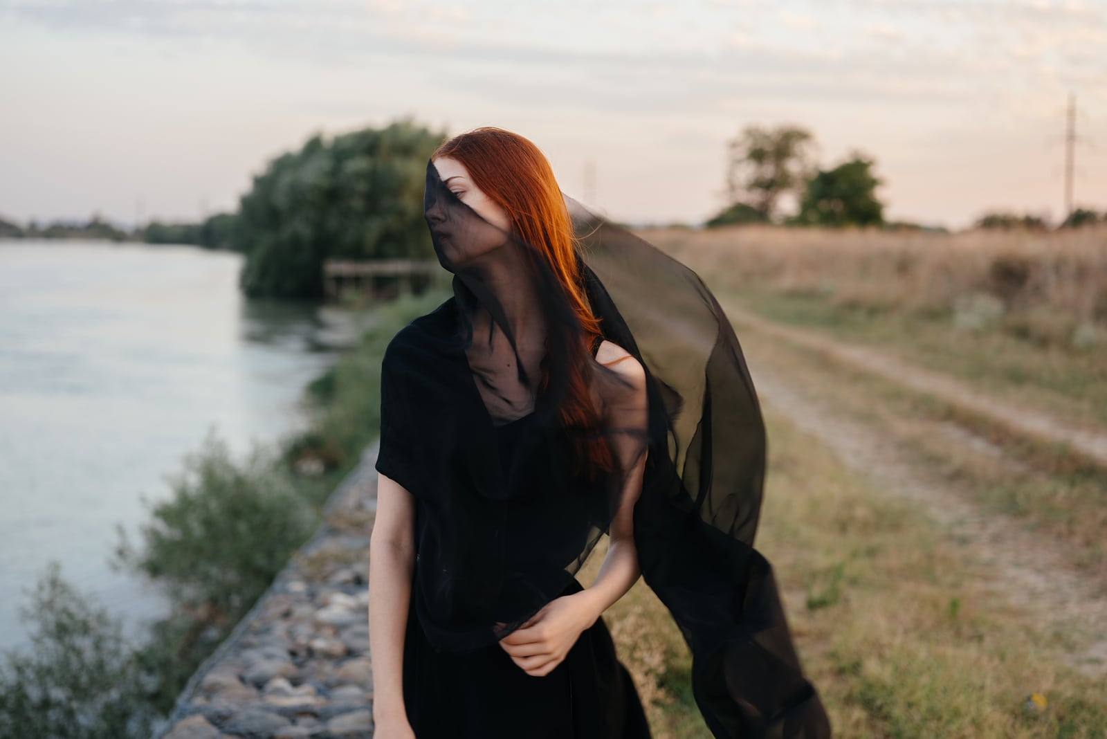 woman in a dark dress and with a black veil near the river