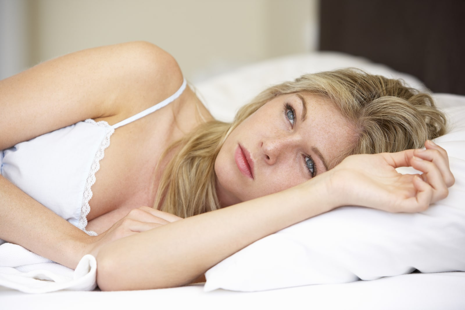 sad blond woman lying in bed