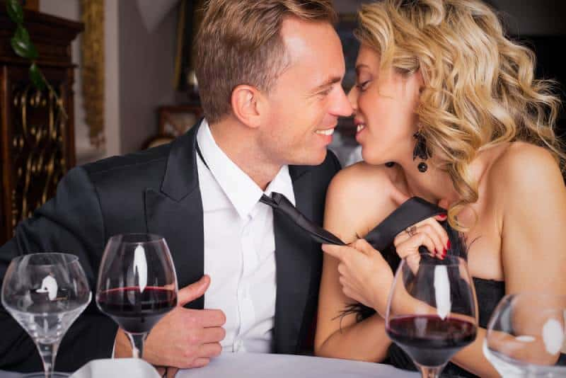 woman pulling man into kiss by tie