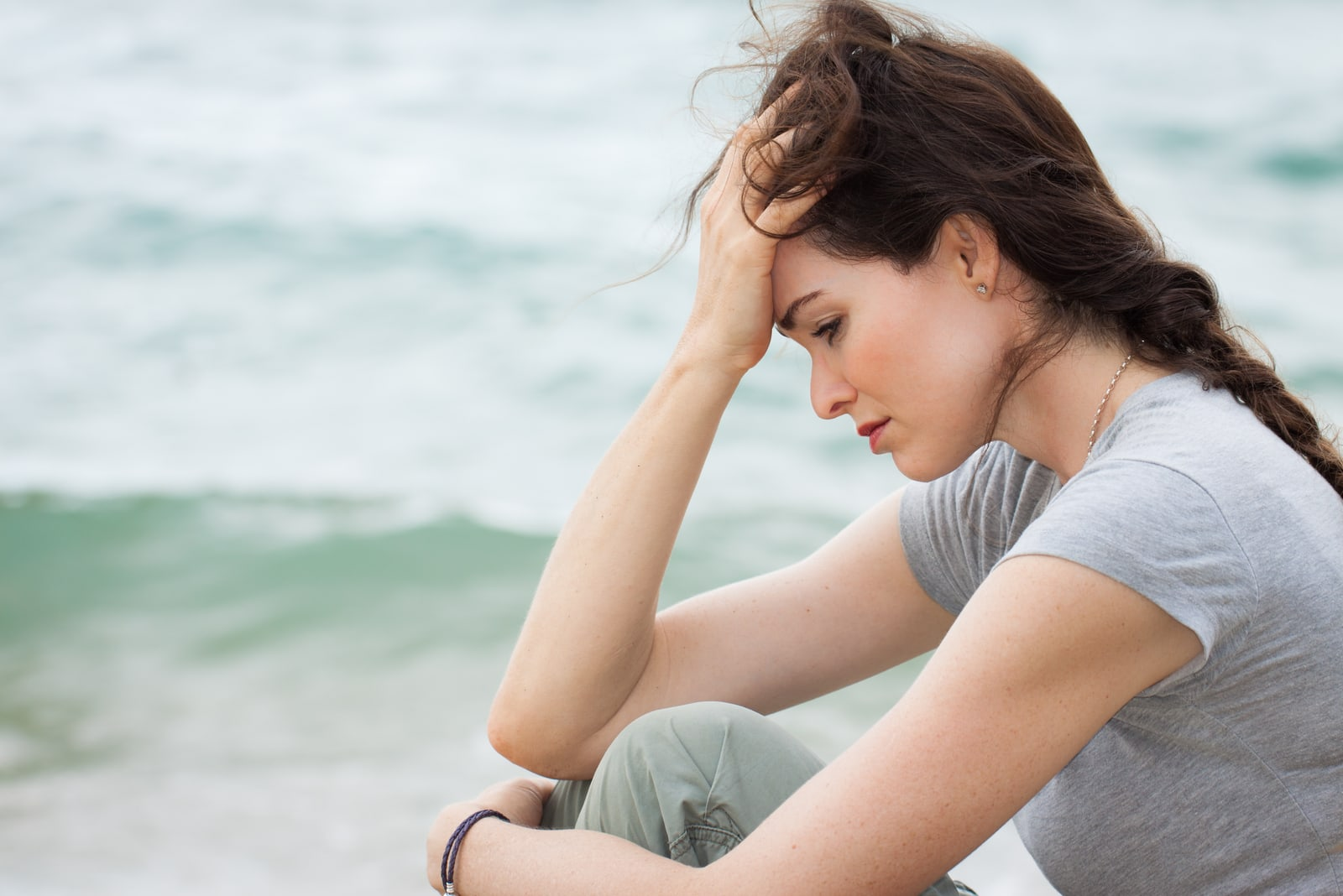 sad and worried woman sitting on the beach