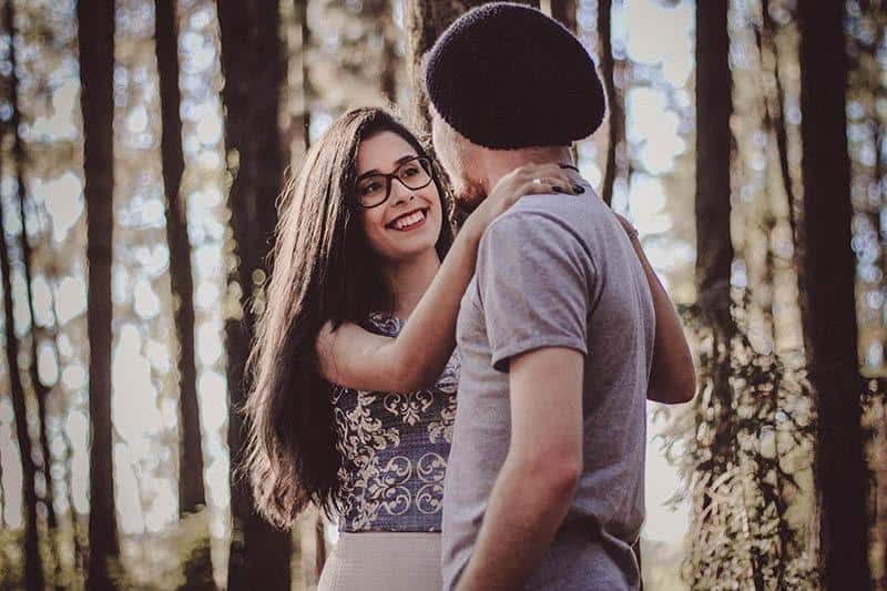 young woman wearing glasses hugging man