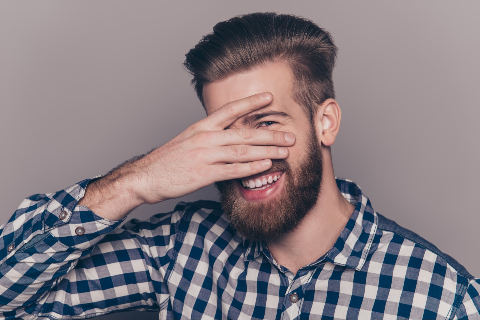 Funny cute young man with beard hiding his face
