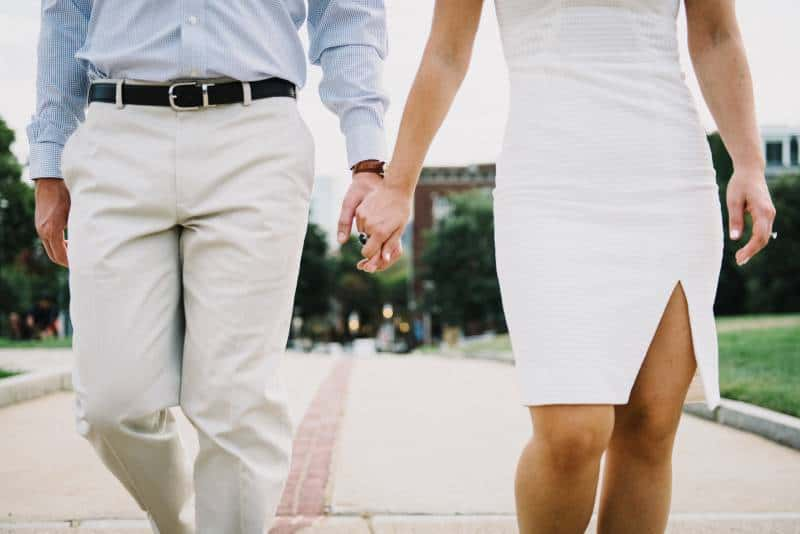Man and woman holding hands outside