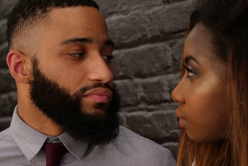 Man stares at woman near gray wall