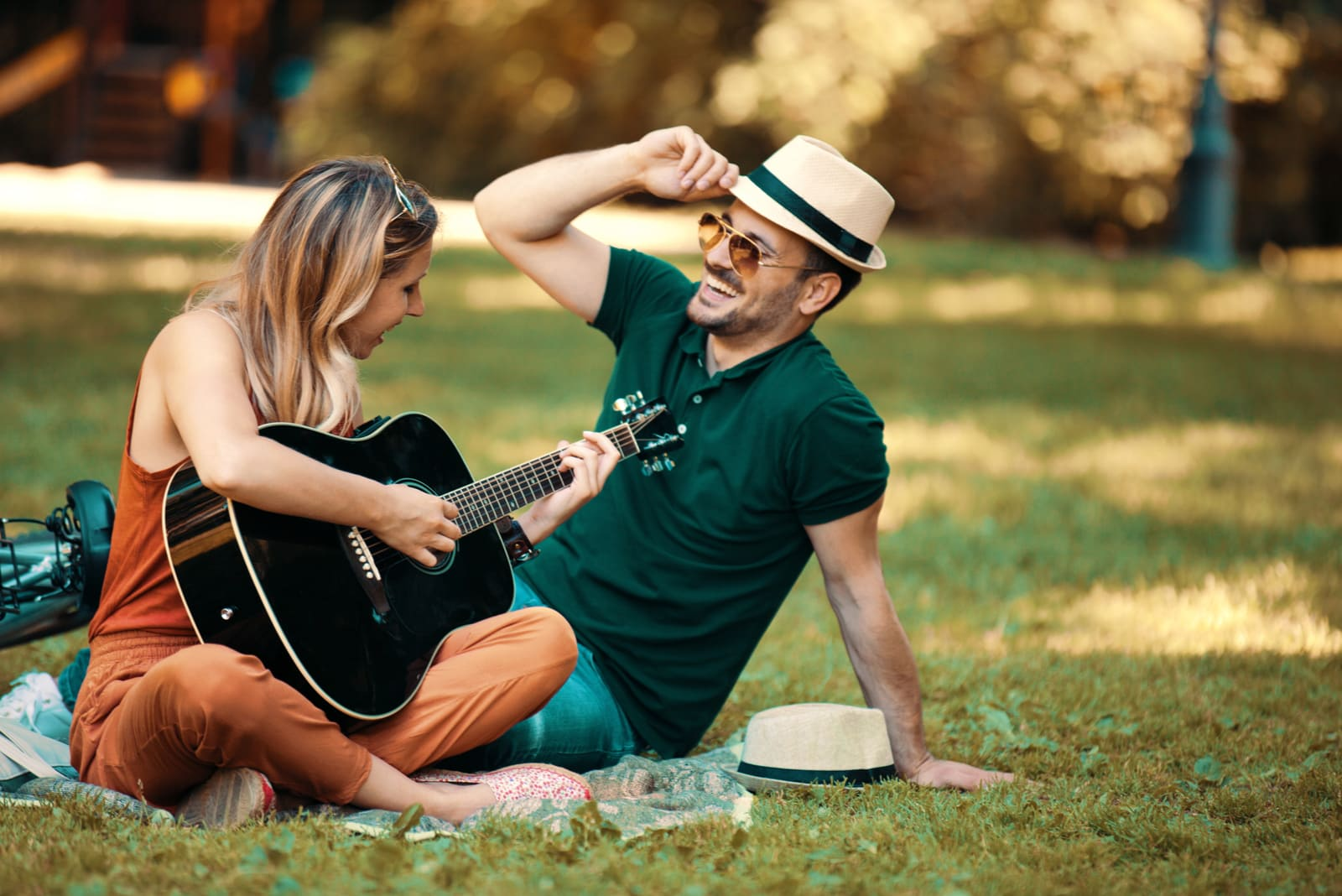 Young couple enjoying park and playing guitar