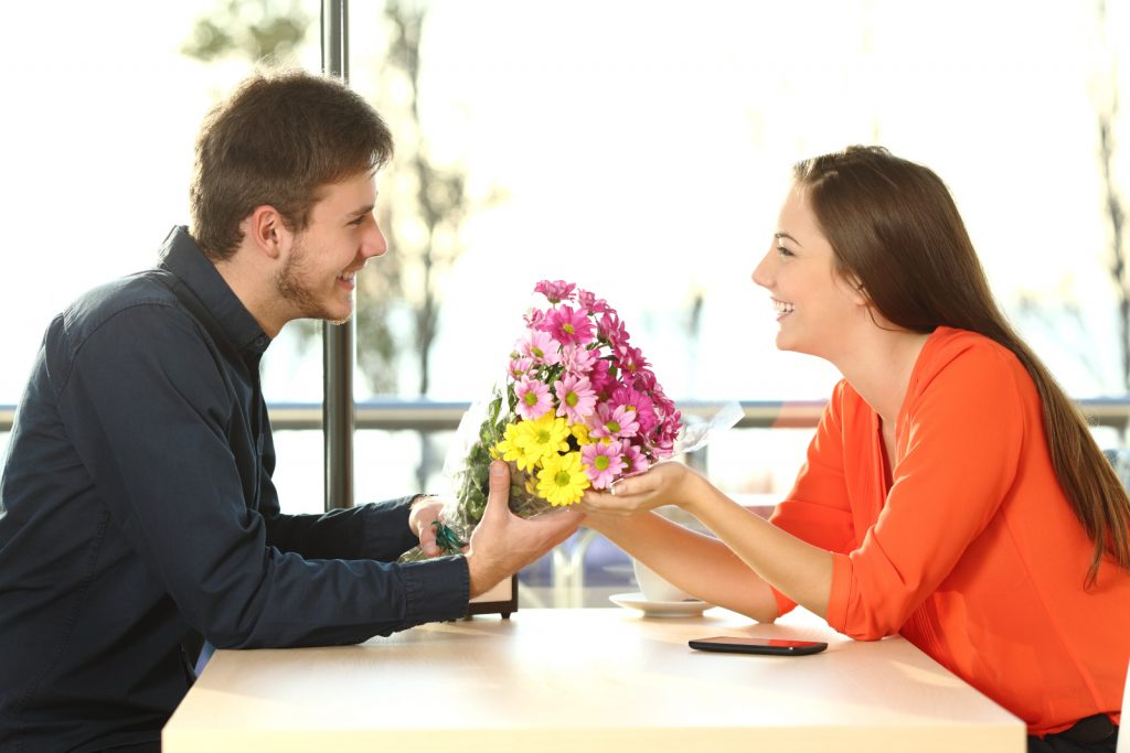 a man gives flowers to a girl