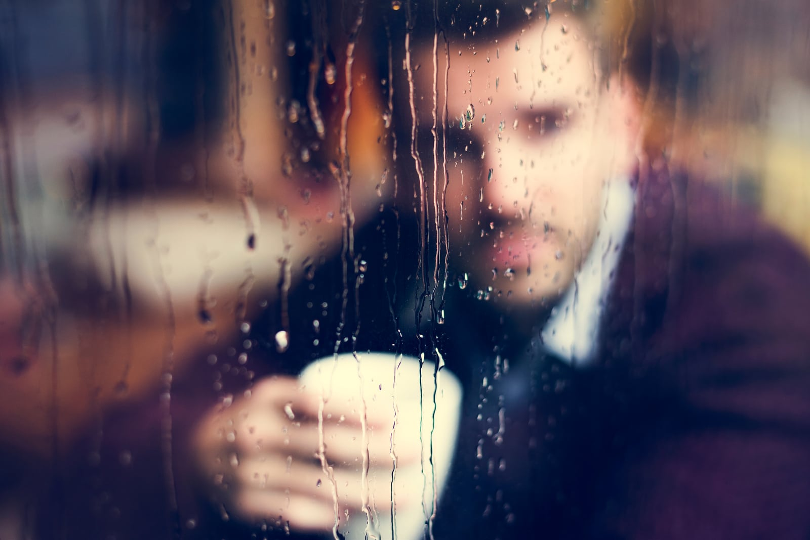a man sits by the window and drinks coffee