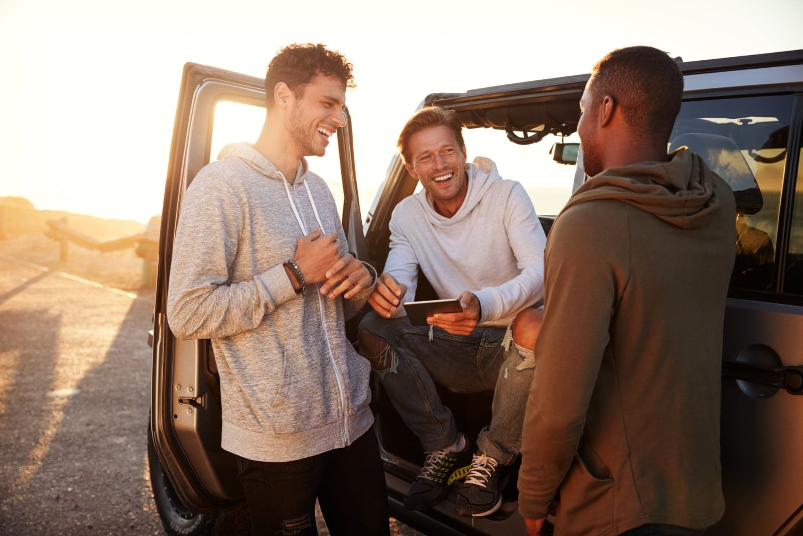 a man stands with friends next to a car and laughs