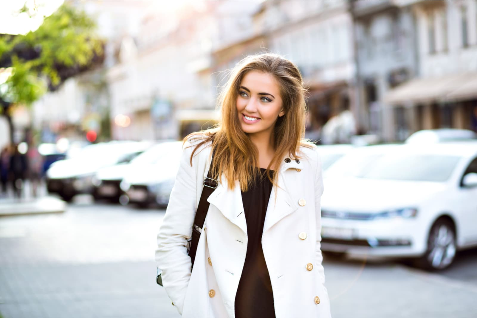 a woman with long brown hair in a white coat walks down the street