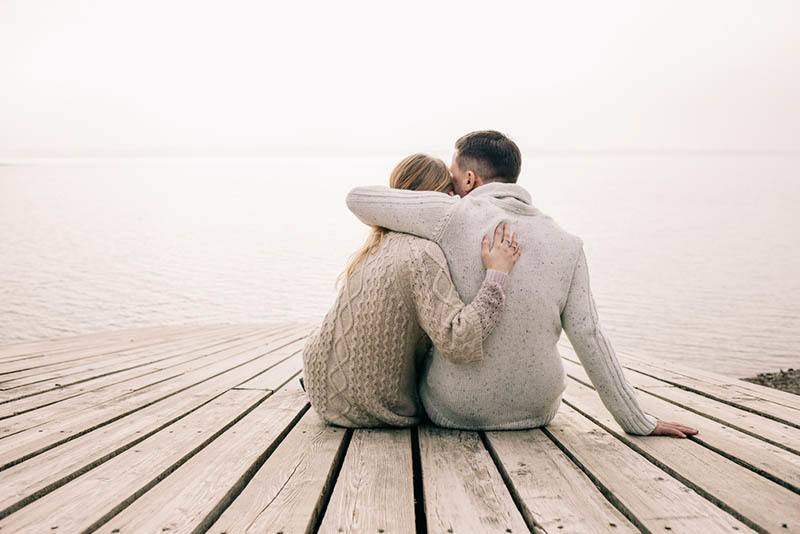 back view of couple sitting on wooden dock and hugging