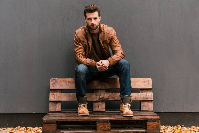 confident fashion man sitting on wooden bench