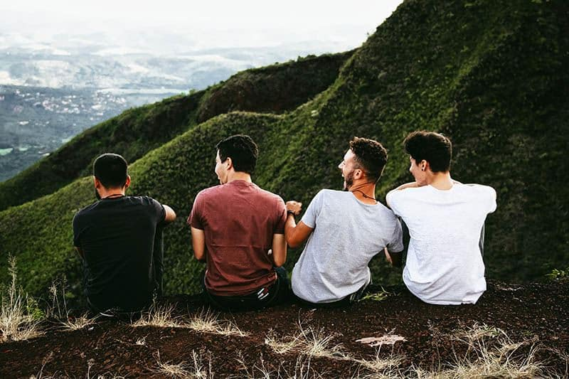 friends sitting in front of hills