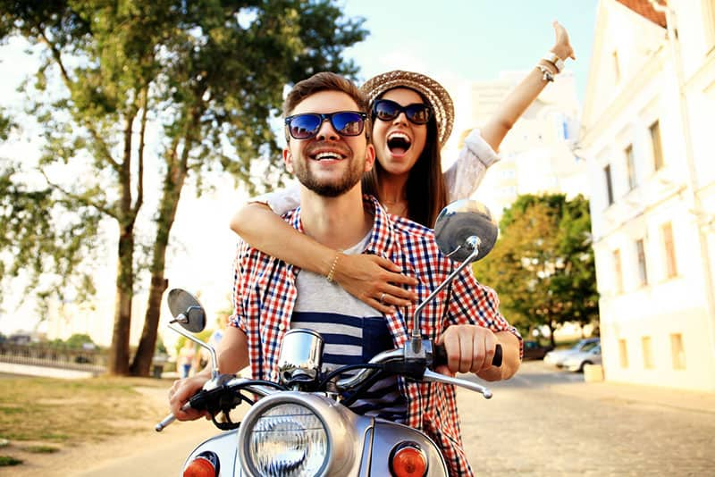 happy couple driving on motorbike