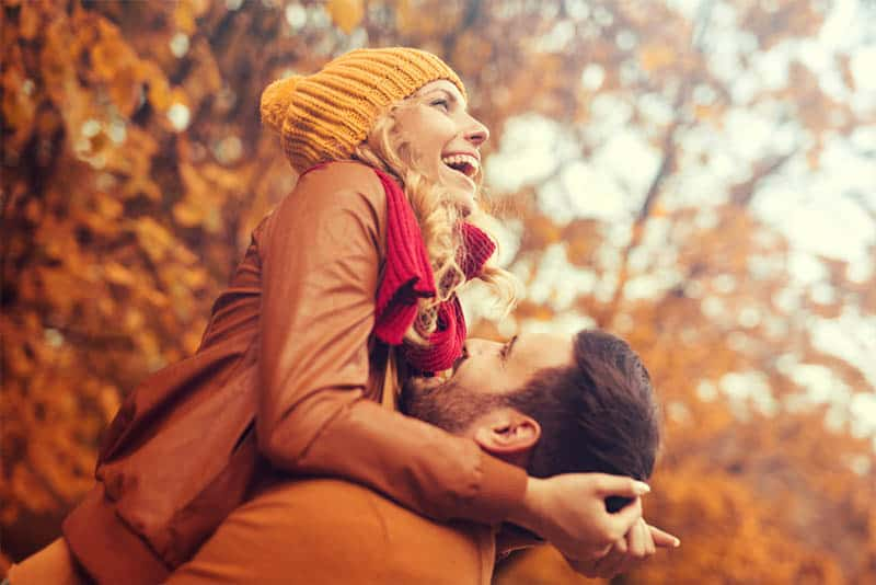 happy man pickup woman during autumn