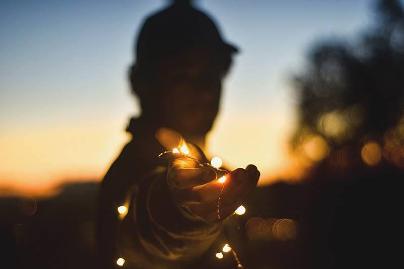 man holding christamas lights