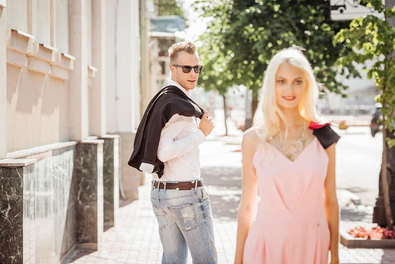 man looking at blond woman on the street