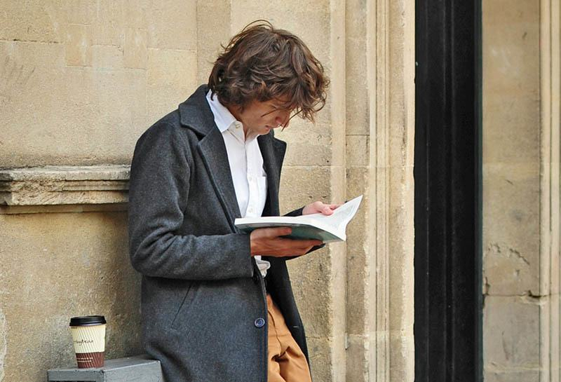 man reading a book while leaning on the wall