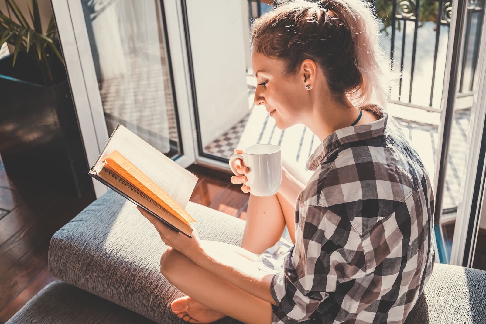 pretty woman sitting at opened window drinking coffee and reading a book