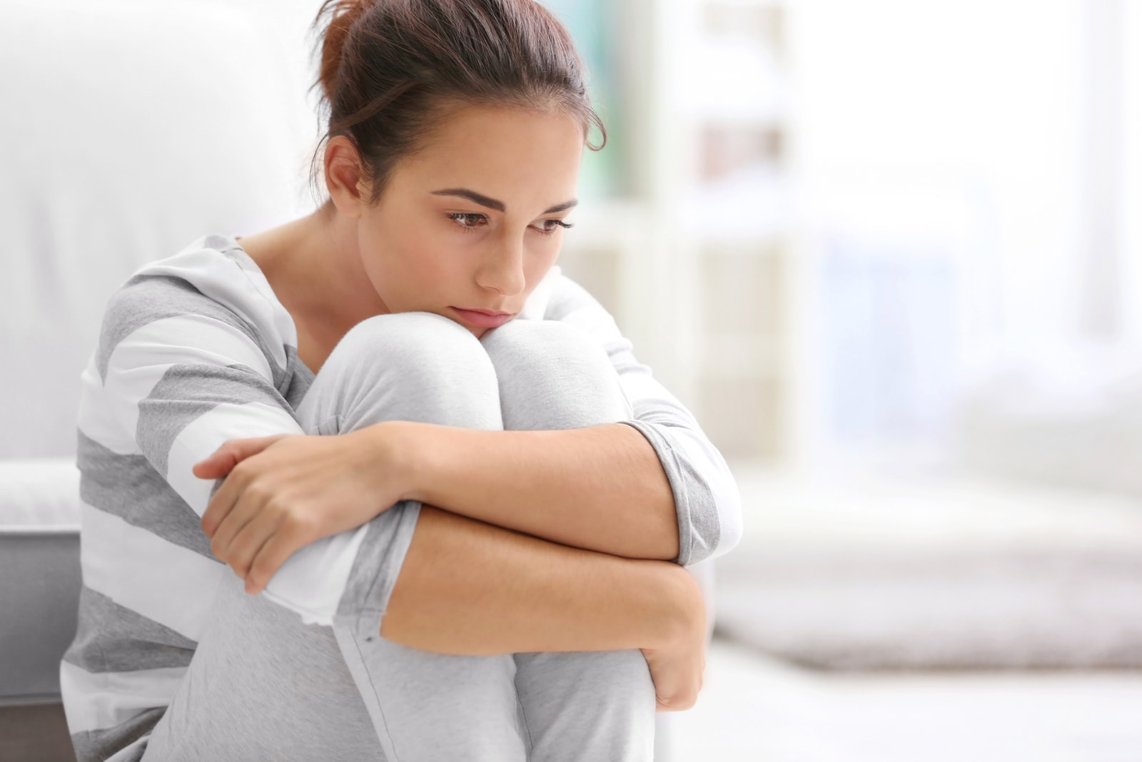 sad mindful woman sitting alone on the couch