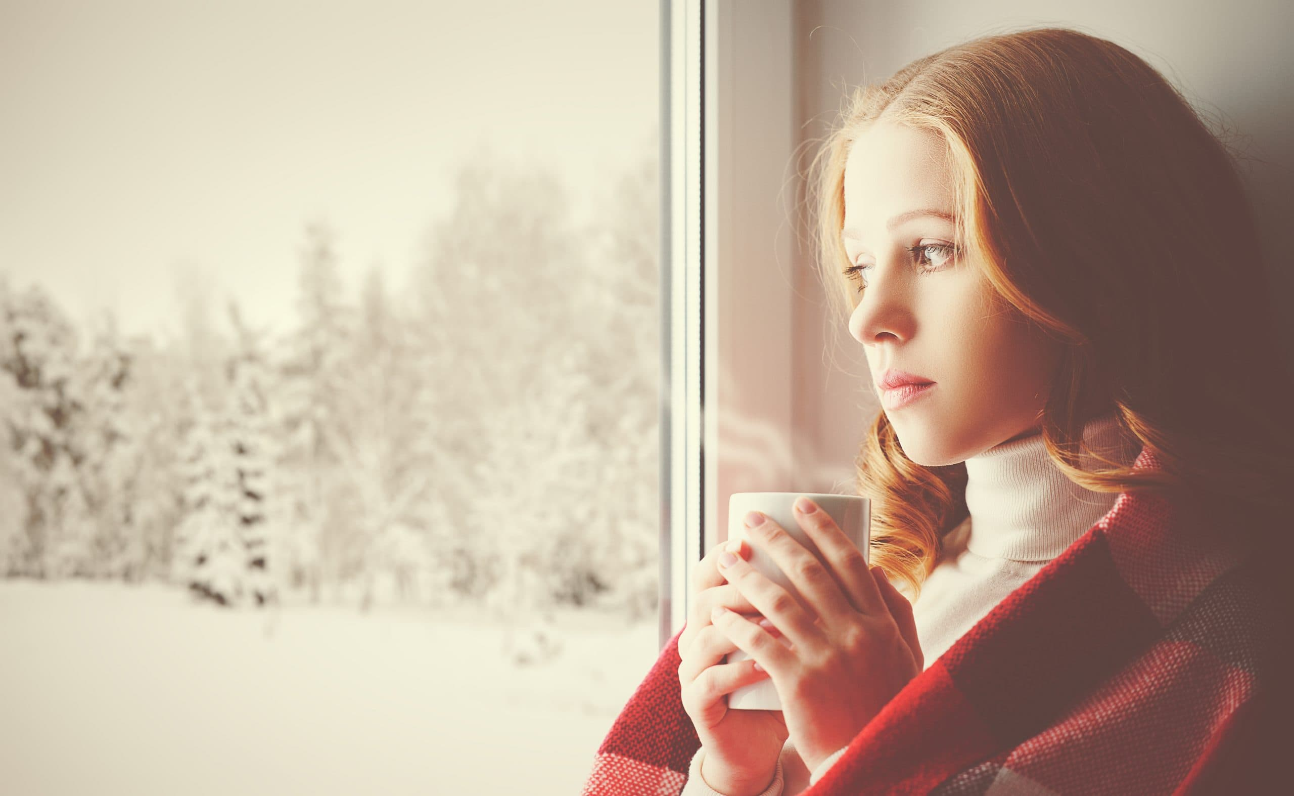 sad woman holding cup of tea and looking through the window