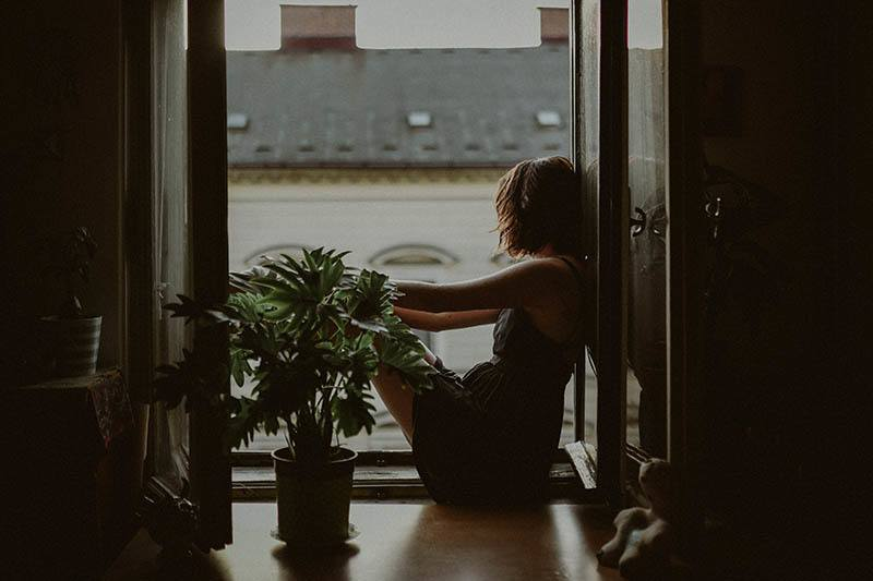 sad woman sitting by the window and plant