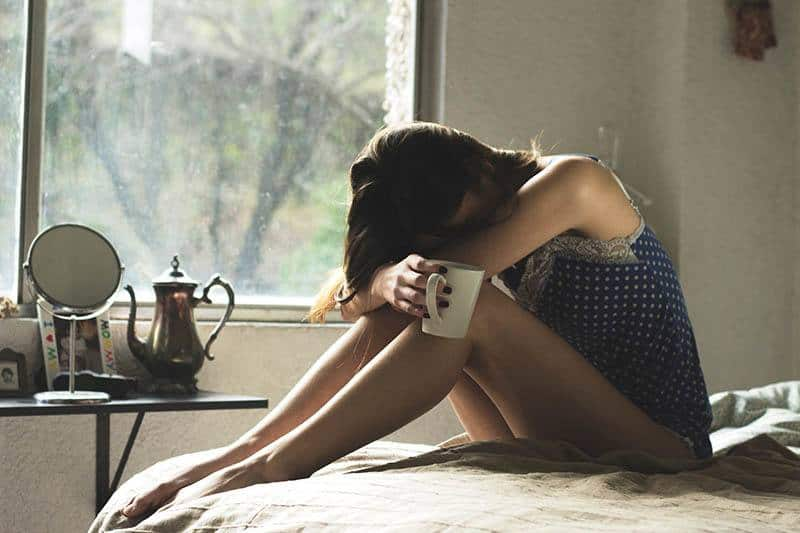 sad woman sitting on the bed holding a cup