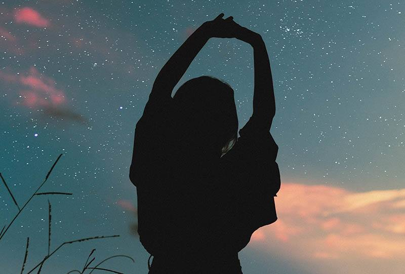 silhouette of woman raising her hands up to stars