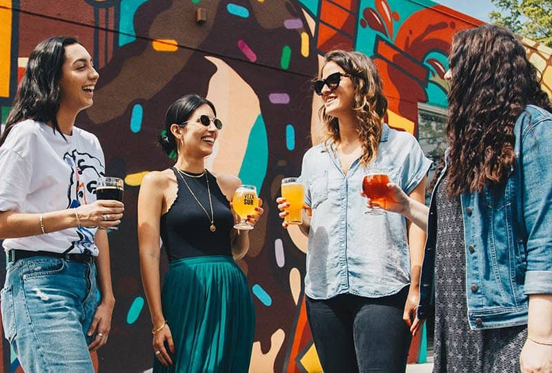 smiling female friends standing outside and holding glasses of juice