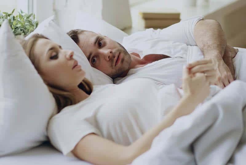 thoughtful couple lying on bed