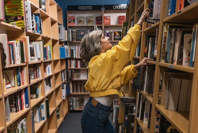 woman reaching a book on the shelf