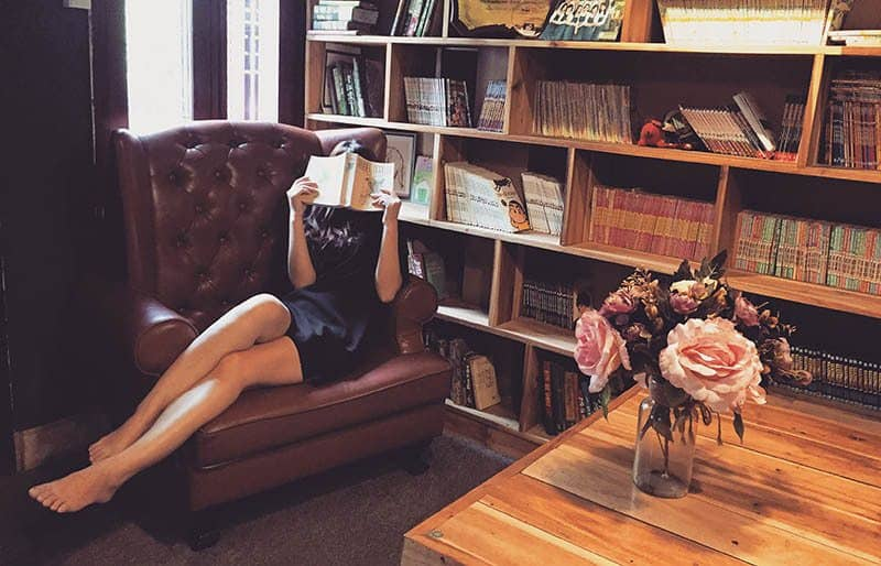 woman sitting on sofa while covering face with book