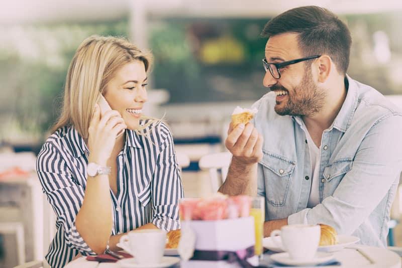 woman talking on phone while man smiling