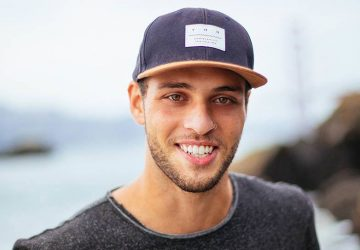 portrait of smiling man wearing hat outside