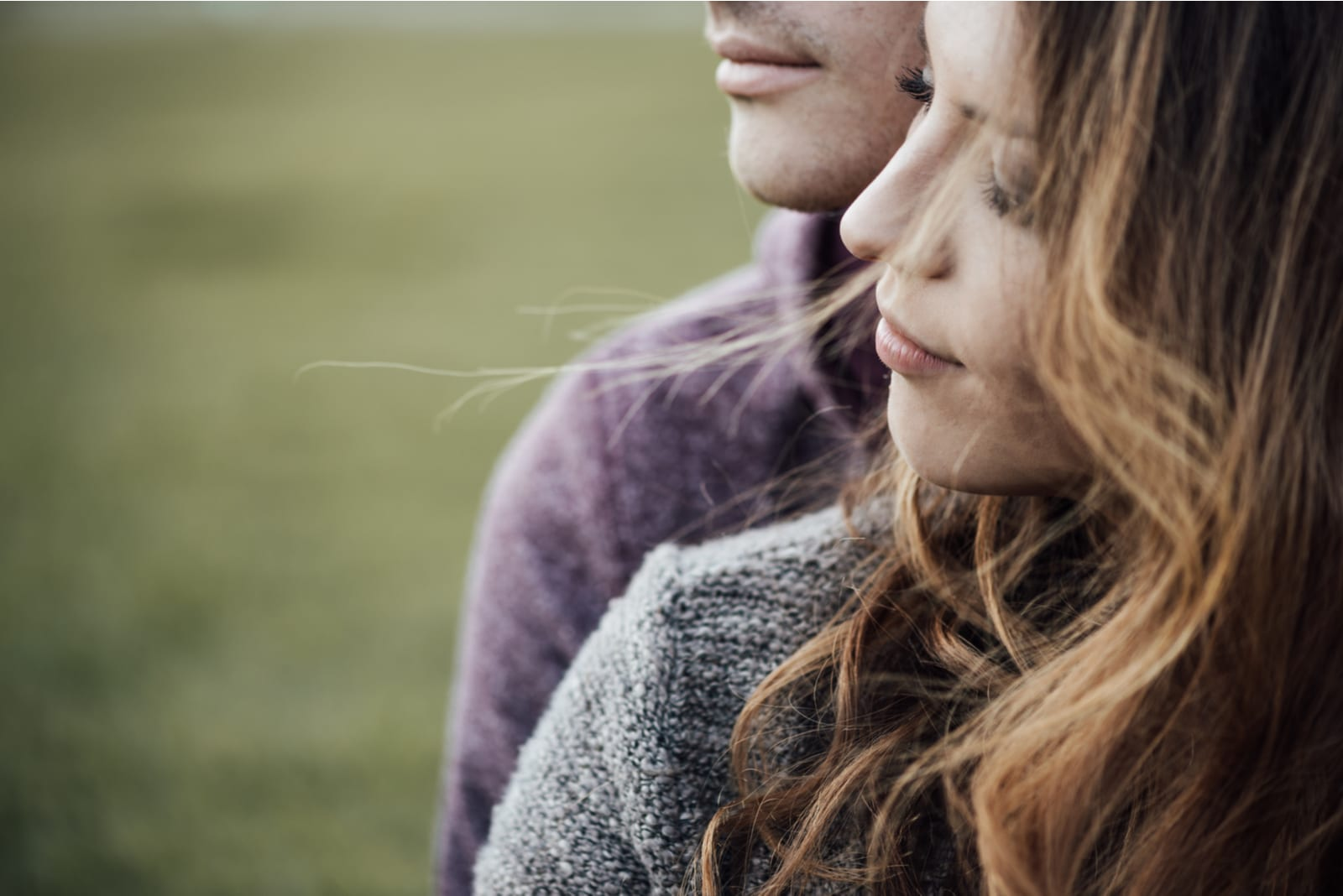 Young loving couple outdoors sitting on grass
