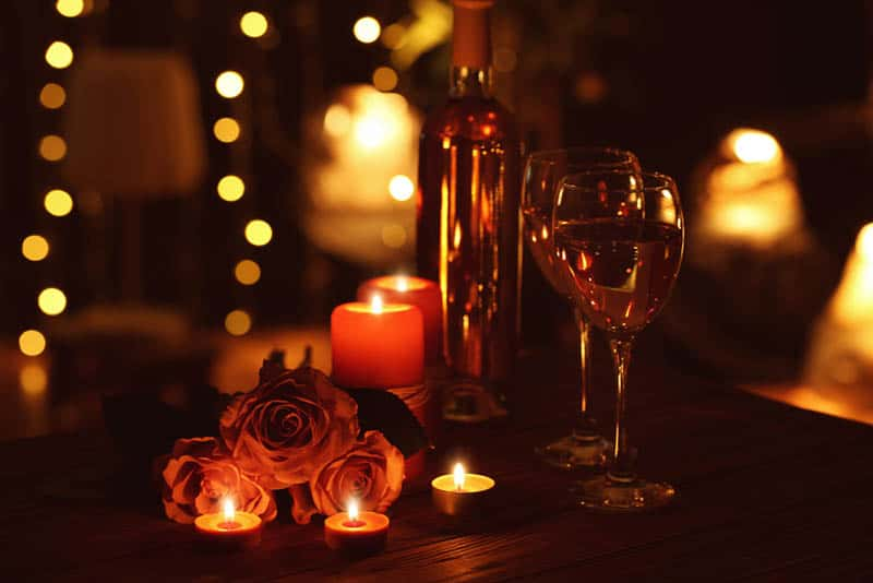 Beautiful romantic composition with candles roses and glasses of wine