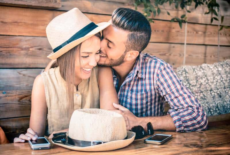 Man kisses smiling woman on cheek in cafe