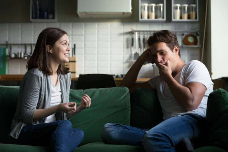 Young man yawns and is bored when he listens to the excited woman talking