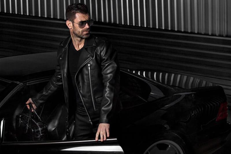 alpha man standing in front of open car's doors